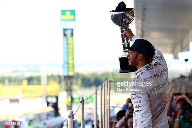 Lewis Hamilton of Great Britain and Mercedes GP celebrates on the podium after winning the Formula One Grand Prix of Japan at Suzuka Circuit on...