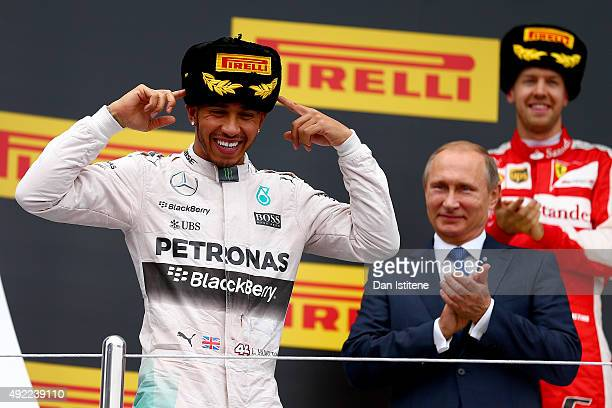 Lewis Hamilton of Great Britain and Mercedes GP celebrates on the podium next to President of Russia Vladimir Putin and Sebastian Vettel of Germany...