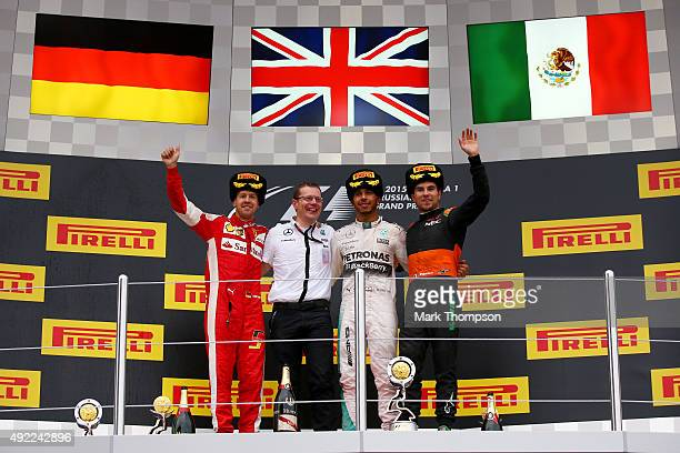 Lewis Hamilton of Great Britain and Mercedes GP celebrates on the podium next to Sebastian Vettel of Germany and Ferrari and Sergio Perez of Mexico...