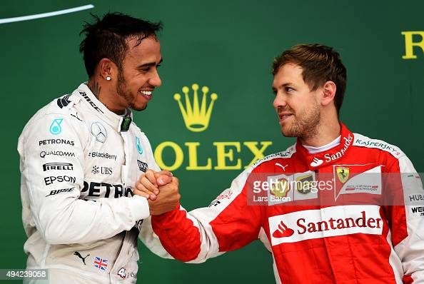 Lewis Hamilton of Great Britain and Mercedes GP celebrates on the podium with Sebastian Vettel of Germany and Ferrari after winning the United States...