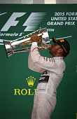 Lewis Hamilton of Great Britain and Mercedes GP celebrates on the podium after winning the United States Formula One Grand Prix and the championship...