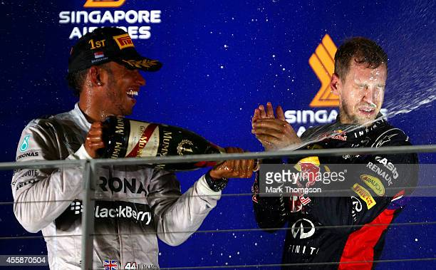 Lewis Hamilton of Great Britain and Mercedes GP celebrates with Sebastian Vettel of Germany and Infiniti Red Bull Racing on the podium after winning...