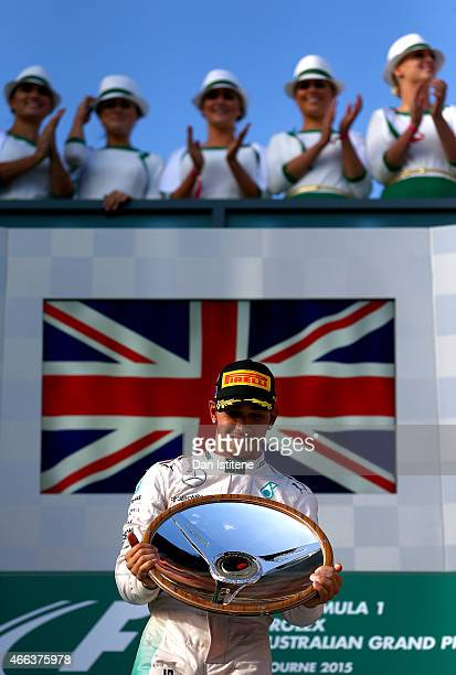 Lewis Hamilton of Great Britain and Mercedes GP celebrates with the trophy on the podium after winning the Australian Formula One Grand Prix at...