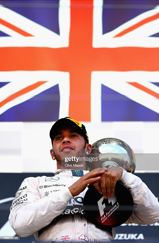 Lewis Hamilton of Great Britain and Mercedes GP celebrates with the trophy on the podium after winning the Formula One Grand Prix of Japan at Suzuka...