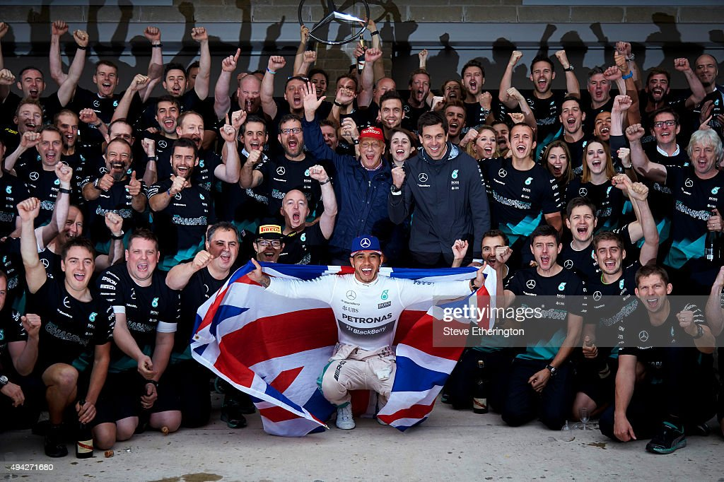 Lewis Hamilton of Great Britain and Mercedes GP celebrates with the team in the pit lane after winning the United States Formula One Grand Prix and the championship at Circuit of The Americas on October 25, 2015 in Austin, United States.