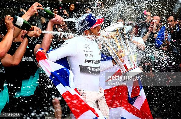 Lewis Hamilton of Great Britain and Mercedes GP celebrates with the team in the pit lane after winning the United States Formula One Grand Prix and...