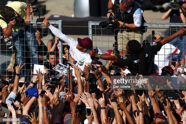 Lewis Hamilton of Great Britain and Mercedes GP celebrates with the fans on the pit straight after winning the Canadian Formula One Grand Prix at...