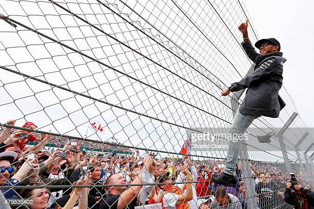 Lewis Hamilton of Great Britain and Mercedes GP climbs a fence to wave to the fans before the Formula One Grand Prix of Great Britain at Silverstone...