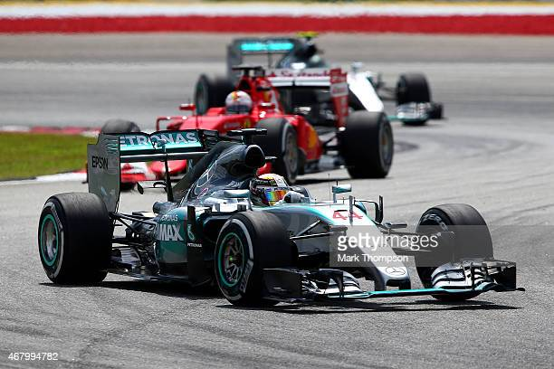 Lewis Hamilton of Great Britain and Mercedes GP drives ahea dof Nico Rosberg of Germany and Mercedes GP and Sebastian Vettel of Germany and Ferrari...