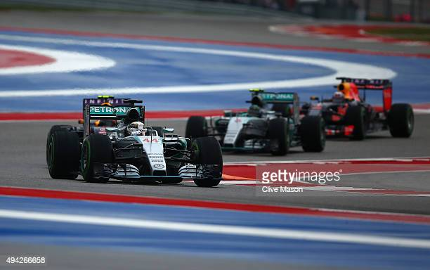 Lewis Hamilton of Great Britain and Mercedes GP drives ahead of Daniil Kvyat of Russia and Infiniti Red Bull Racing Nico Rosberg of Germany and...