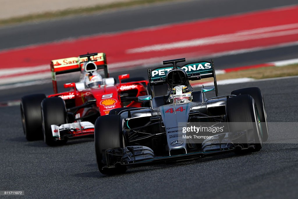 Lewis Hamilton of Great Britain and Mercedes GP drives ahead of Sebastian Vettel of Germany and Ferrari during day one of F1 winter testing at...