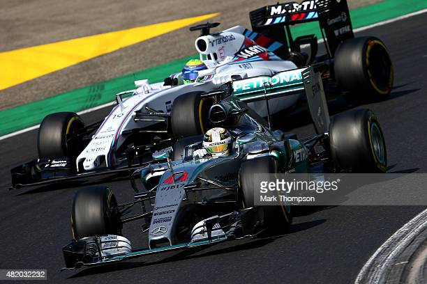 Lewis Hamilton of Great Britain and Mercedes GP drives next to Felipe Massa of Brazil and Williams during the Formula One Grand Prix of Hungary at...