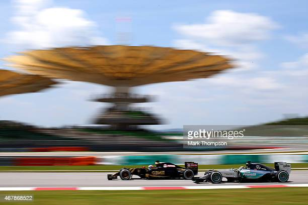 Lewis Hamilton of Great Britain and Mercedes GP drives next to Romain Grosjean of France and Lotus during final practice for the Malaysia Formula One...