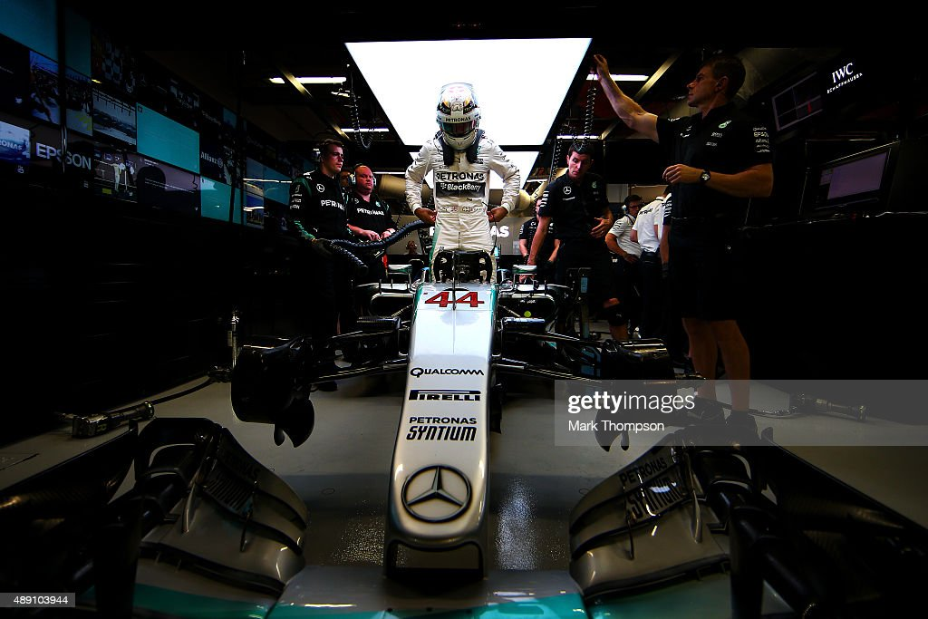 Lewis Hamilton of Great Britain and Mercedes GP gets into his car in the garage during qualifying for the Formula One Grand Prix of Singapore at Marina Bay Street Circuit on September 19, 2015 in Singapore.