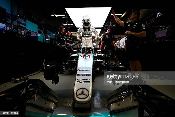 Lewis Hamilton of Great Britain and Mercedes GP gets into his car in the garage during qualifying for the Formula One Grand Prix of Singapore at...