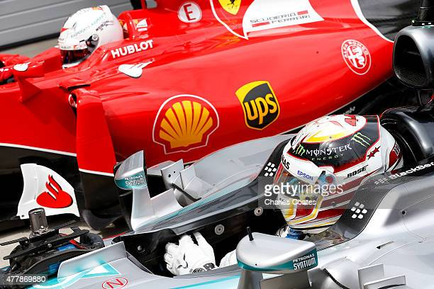 Lewis Hamilton of Great Britain and Mercedes GP gets out of his car in Parc Ferme next to Sebastian Vettel of Germany and Ferrari after claiming pole...