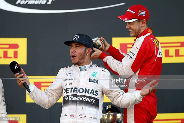 Lewis Hamilton of Great Britain and Mercedes GP has champagne poured down his back by Sebastian Vettel of Germany and Ferrari on the podium after...