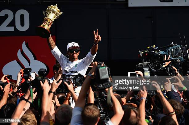 Lewis Hamilton of Great Britain and Mercedes GP his held aloft by his team mates as he holds the old British Grand Prix Trophy while he celebrates...