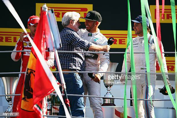 Lewis Hamilton of Great Britain and Mercedes GP hugs film director George Lucas on the podium after winning the Formula One Grand Prix of Italy at...
