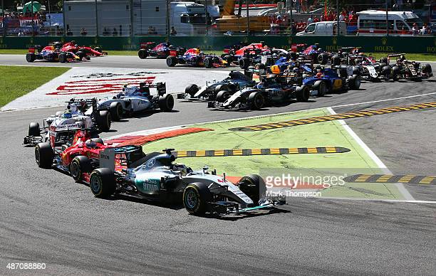Lewis Hamilton of Great Britain and Mercedes GP leads Sebastian Vettel of Germany and Ferrari into the first corner during the Formula One Grand Prix...
