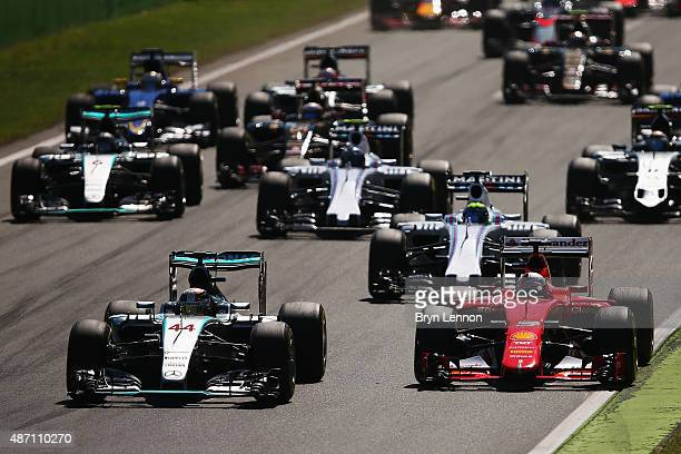 Lewis Hamilton of Great Britain and Mercedes GP leads the field into the first corner ahead of Sebastian Vettel of Germany and Ferrari during the...