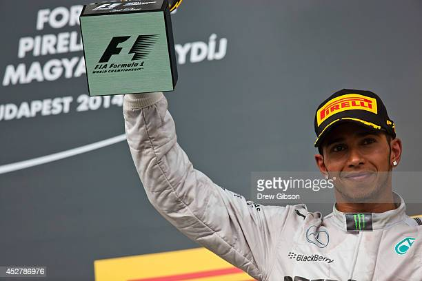 Lewis Hamilton of Great Britain and Mercedes GP lifts his trophy on the podium after claiming third in the Hungarian Formula One Grand Prix at...