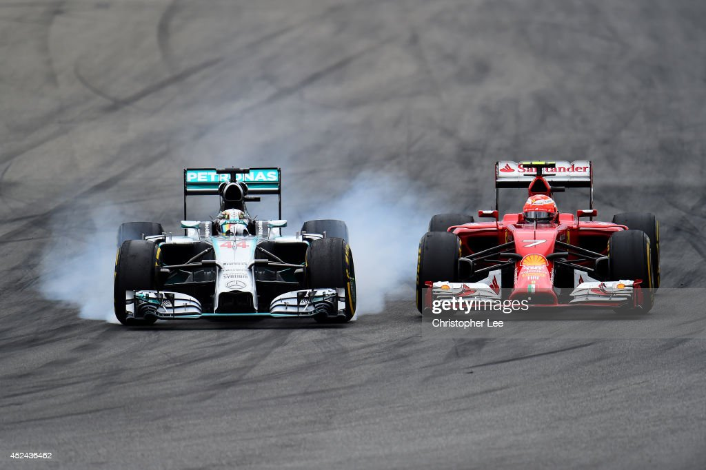 <a gi-track='captionPersonalityLinkClicked' href=/galleries/search?phrase=Lewis+Hamilton+-+Racecar+Driver&family=editorial&specificpeople=586983 ng-click='$event.stopPropagation()'>Lewis Hamilton</a> of Great Britain and Mercedes GP locks up as he passes <a gi-track='captionPersonalityLinkClicked' href=/galleries/search?phrase=Kimi+Raikkonen&family=editorial&specificpeople=201904 ng-click='$event.stopPropagation()'>Kimi Raikkonen</a> of Finland and Ferrari during the German Grand Prix at Hockenheimring on July 20, 2014 in Hockenheim, Germany.