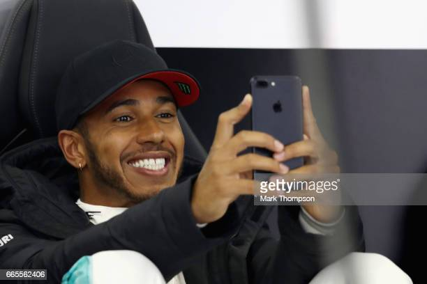 Lewis Hamilton of Great Britain and Mercedes GP on his phone in the garage during practice for the Formula One Grand Prix of China at Shanghai...
