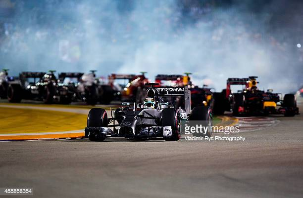 Lewis Hamilton of Great Britain and Mercedes GP Petronas leads in the first corner after the start of the Singapore Formula One Grand Prix at Marina...