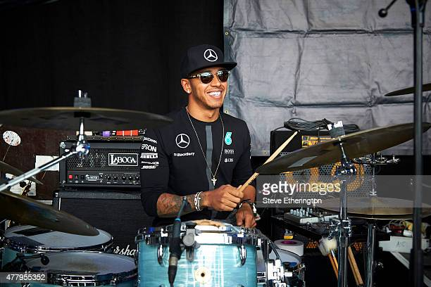 Lewis Hamilton of Great Britain and Mercedes GP plays the drums on stage during a fan event after qualifying for the Formula One Grand Prix of...