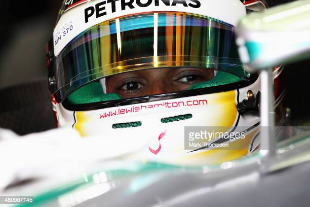 Lewis Hamilton of Great Britain and Mercedes GP prepares to drive while wearing a sticker on his helmet in memory of Malaysian Airlines flight MH370...