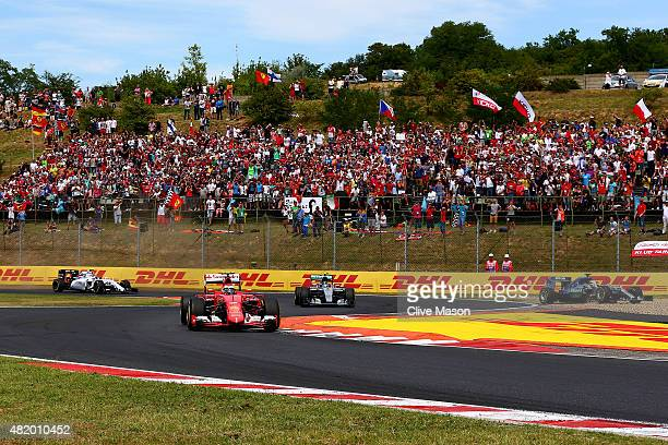 Lewis Hamilton of Great Britain and Mercedes GP runs across the gravel as Kimi Raikkonen of Finland and Ferrari and Nico Rosberg of Germany and...