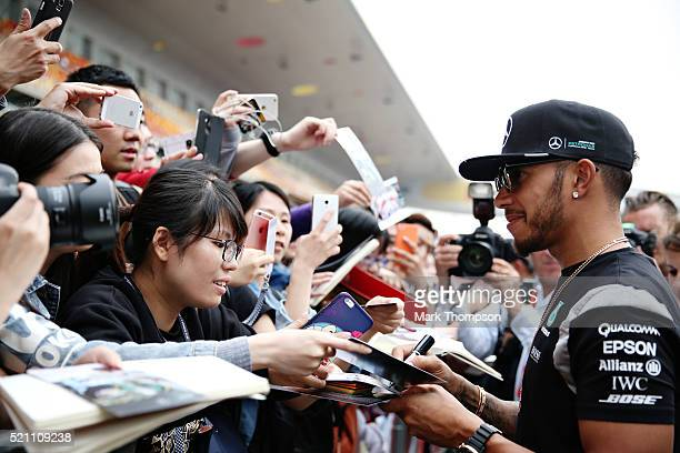 Lewis Hamilton of Great Britain and Mercedes GP signs autographs for fans in the Pitlane during previews to the Formula One Grand Prix of China at...