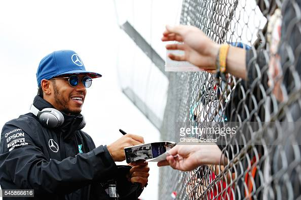 Lewis Hamilton of Great Britain and Mercedes GP signs autographs for fans on the drivers parade before the Formula One Grand Prix of Great Britain at...