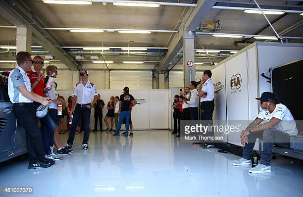 Lewis Hamilton of Great Britain and Mercedes GP sits on his own as he waits with other drivers for the drivers' parade before the Austrian Formula...