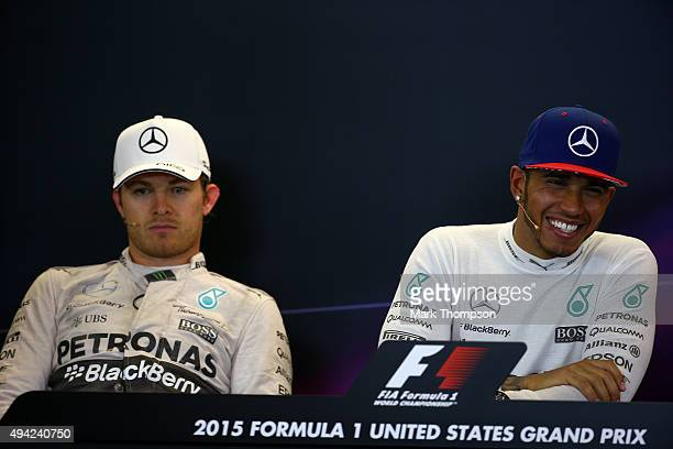 Lewis Hamilton of Great Britain and Mercedes GP smiles next to a dejected Nico Rosberg of Germany and Mercedes GP in a press conference after winning...