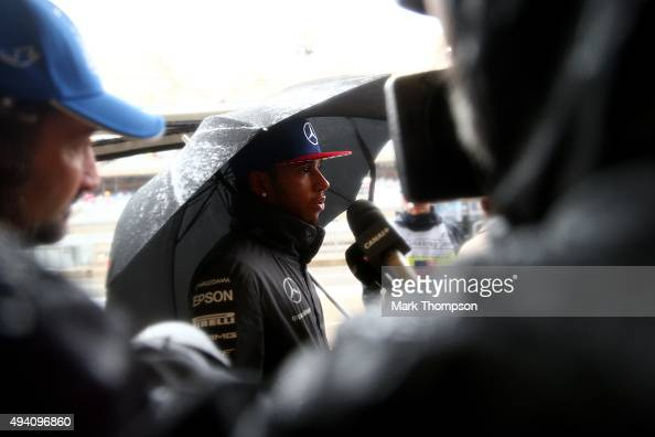 Lewis Hamilton of Great Britain and Mercedes GP speaks with members of the media in the pit lane after qualifying was suspended due to bad weather...
