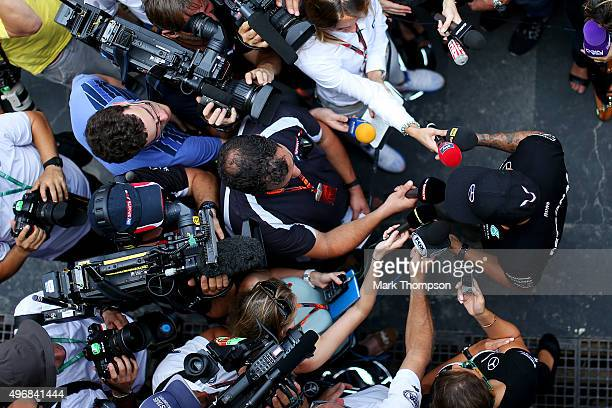 Lewis Hamilton of Great Britain and Mercedes GP speaks with members of the media in the paddock during previews for the Formula One Grand Prix of...