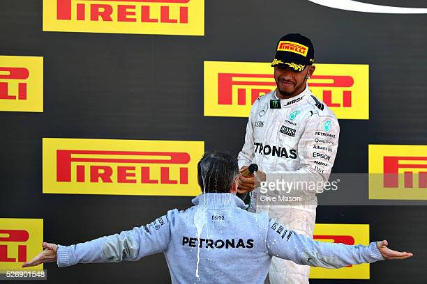 Lewis Hamilton of Great Britain and Mercedes GP sprays Kevin Taylor Mercedes GP Head of Composites on the podium during the Formula One Grand Prix of...