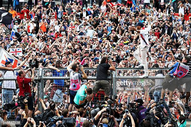 Lewis Hamilton of Great Britain and Mercedes GP stands on top of a fence with a Great Britain flag to celebrate his win with the British fans during...