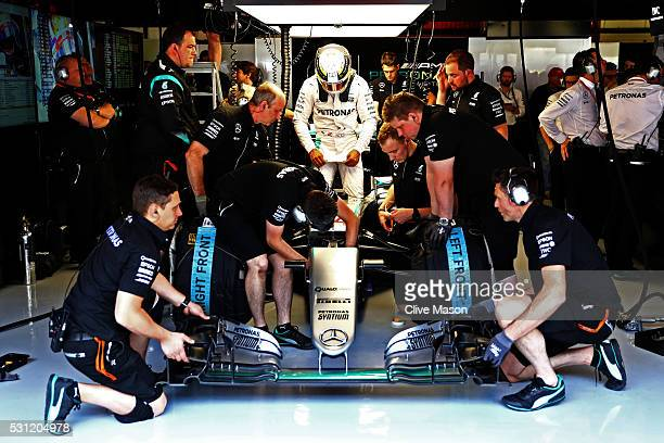 Lewis Hamilton of Great Britain and Mercedes GP surrounded by mechanics in the garage during practice for the Spanish Formula One Grand Prix at...
