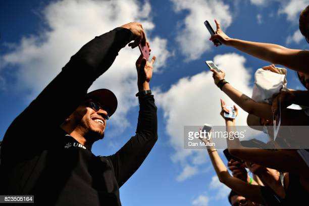 Lewis Hamilton of Great Britain and Mercedes GP takes a photo of fans at the drivers autograph signing session during previews ahead of the Formula...