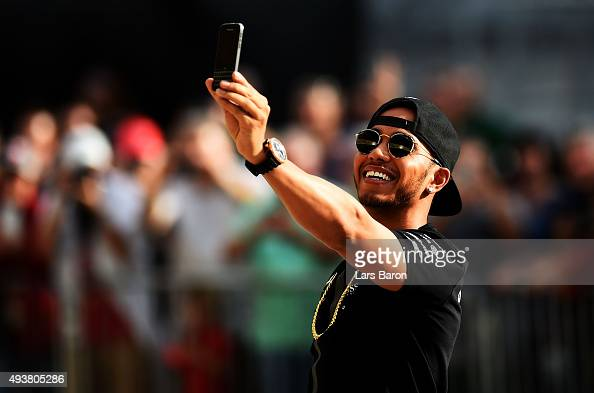 Lewis Hamilton of Great Britain and Mercedes GP takes a selfie in the pit lane after an autograph session during previews to the United States...