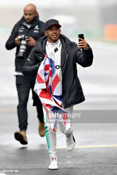 Lewis Hamilton of Great Britain and Mercedes GP takes a video as he runs on the circuit during practice for the Formula One Grand Prix of China at...