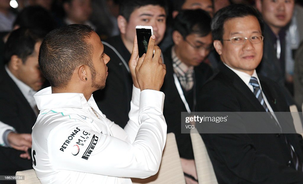 Lewis Hamilton of Great Britain and Mercedes GP takes photos with his smartphone as he attends Petronas promotional event on April 10, 2013 in Shanghai, China.