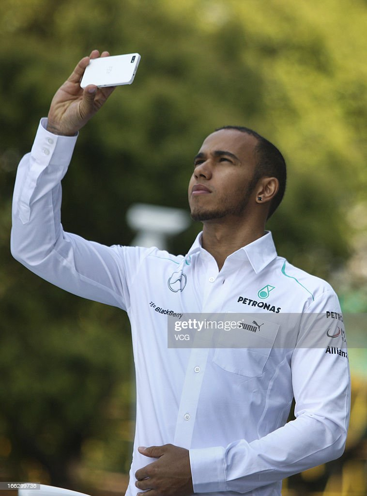 <a gi-track='captionPersonalityLinkClicked' href=/galleries/search?phrase=Lewis+Hamilton+-+Racecar+Driver&family=editorial&specificpeople=586983 ng-click='$event.stopPropagation()'>Lewis Hamilton</a> of Great Britain and Mercedes GP takes photos with his smartphone during the filming of a Mercedes-Benz advertisment in front of Jin Mao Tower on April 10, 2013 in Shanghai, China.