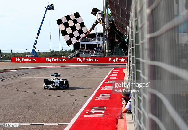 Lewis Hamilton of Great Britain and Mercedes GP takes the checkered flag to seal victory in the United States Formula One Grand Prix at Circuit of...