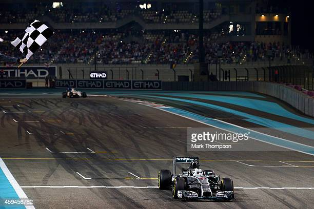 Lewis Hamilton of Great Britain and Mercedes GP takes the checkered flag as he wins the World Championship and the Abu Dhabi Formula One Grand Prix...