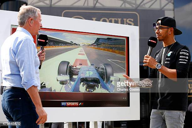 Lewis Hamilton of Great Britain and Mercedes GP talks through his pole position lap with former driver Martin Brundle in the paddock after qualifying...