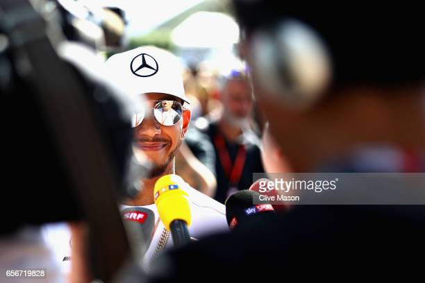Lewis Hamilton of Great Britain and Mercedes GP talks to the media in the Paddock during previews to the Australian Formula One Grand Prix at Albert...